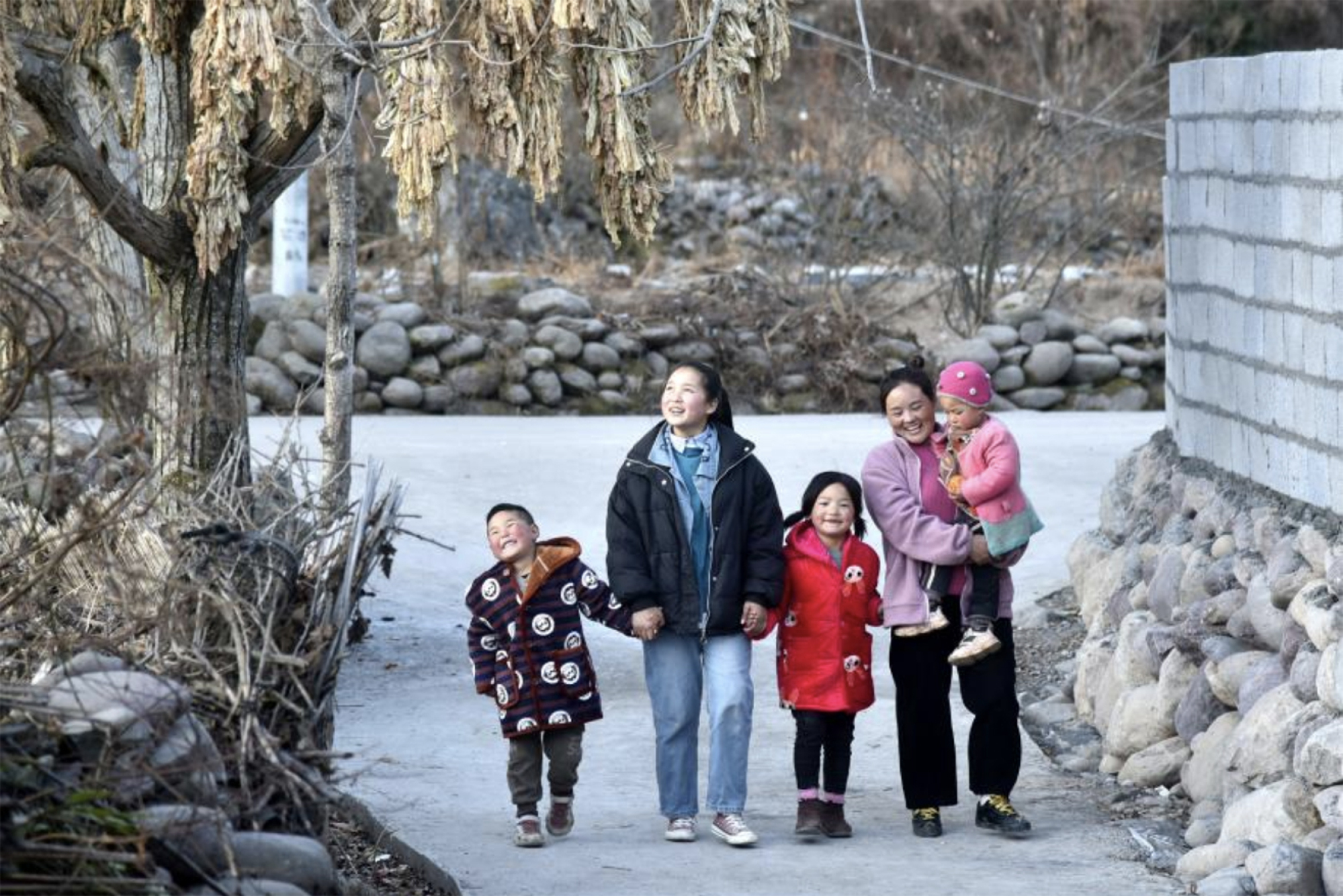Bamu walks with her children on a newly paved concrete road in Taoyuan village. Photo: Xinhua / Zhou Ke