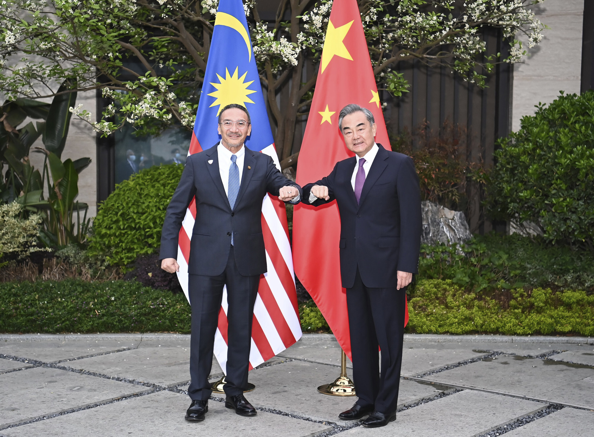 Wang Yi bumps elbows with his Malaysian counterpart Hishammuddin Hussein, one of a series of discussions he held with his Asean counterparts last week. Photo: AP