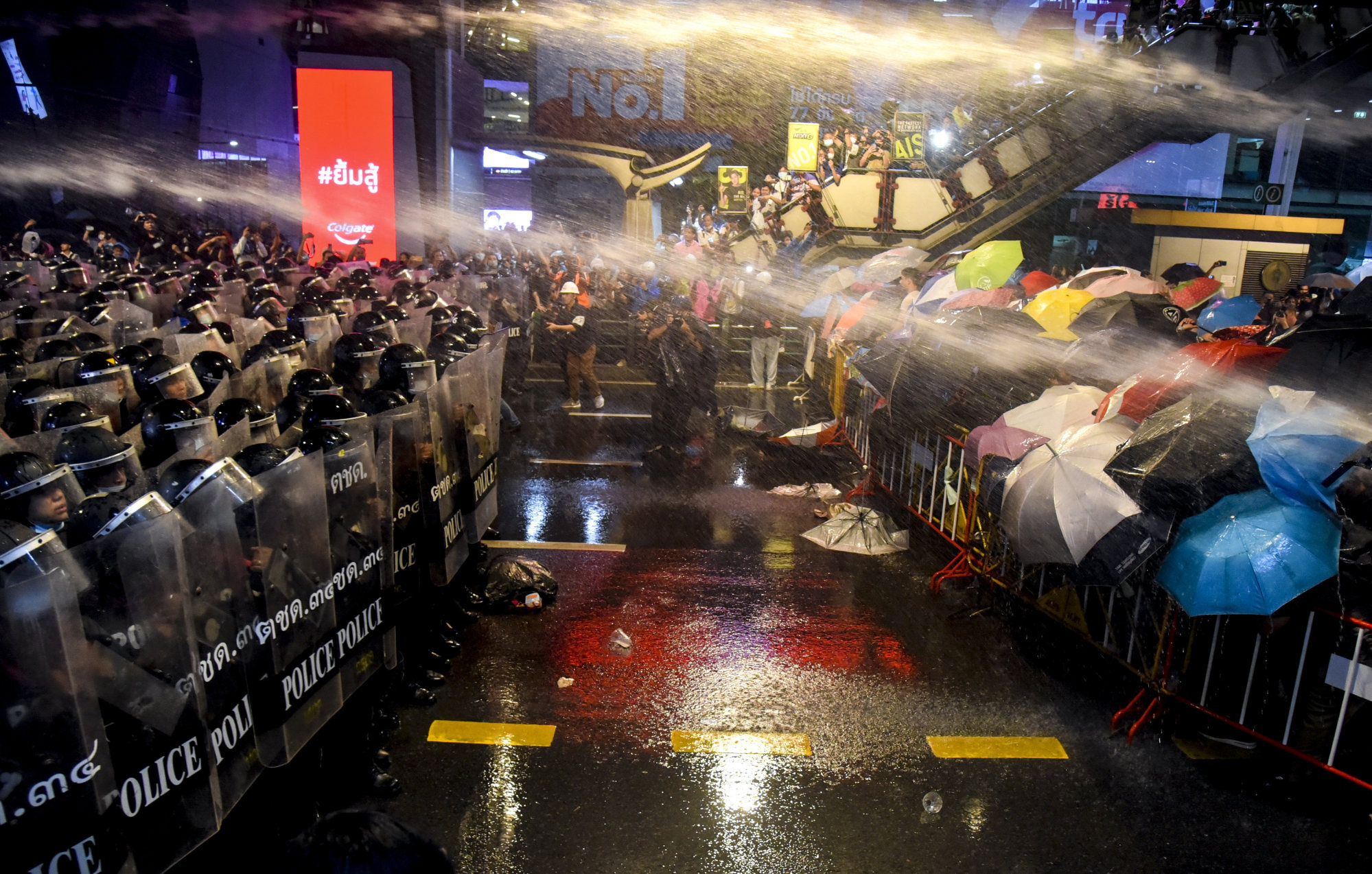 Protesters cover themselves as riot police fire water cannons in Bangkok on October 16, 2020. Photo: ZUMA Wire/dpa