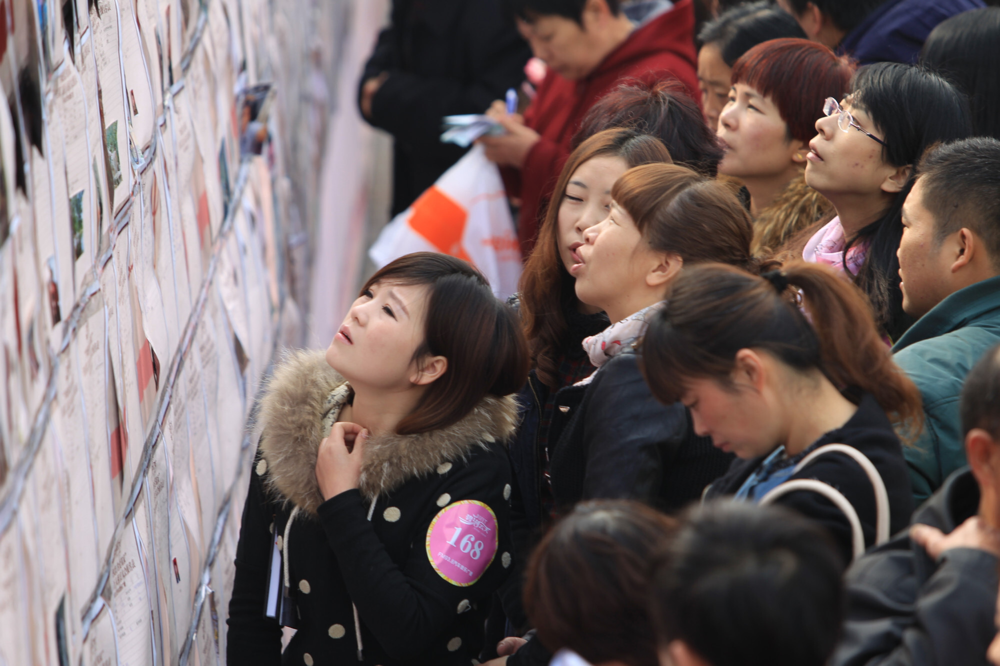 Single participants look at personal information of other bachelors at a mass matchmaking event ahead of Singles Day in Henan province in 2013. Photo: Imaginechina