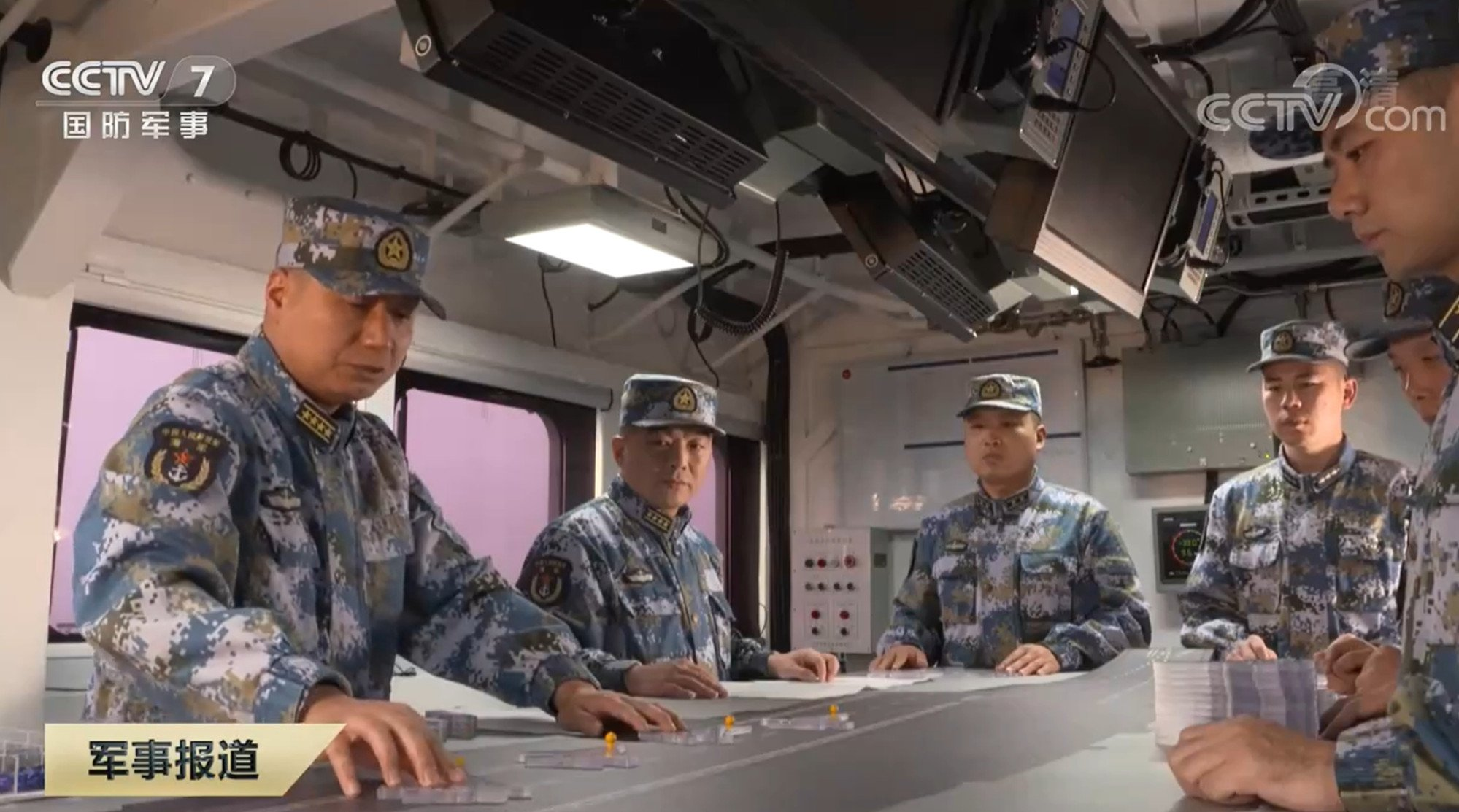"""Lai Yijun, captain of the Shandong (left), and political commissar Song Wenjun (second left) play """"carrier chess"""" using models of J-15 fighters. Photo: CCTV"""