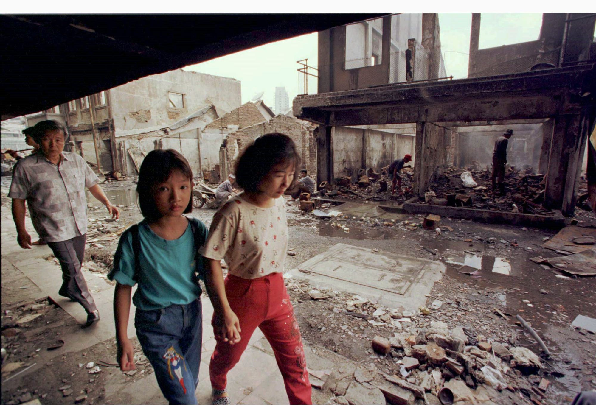 Chinese-Indonesians walk past destroyed houses in Jakarta in 1998 after the area was looted by mobs during riots that precipitated President Suharto's downfall. Photo: Reuters