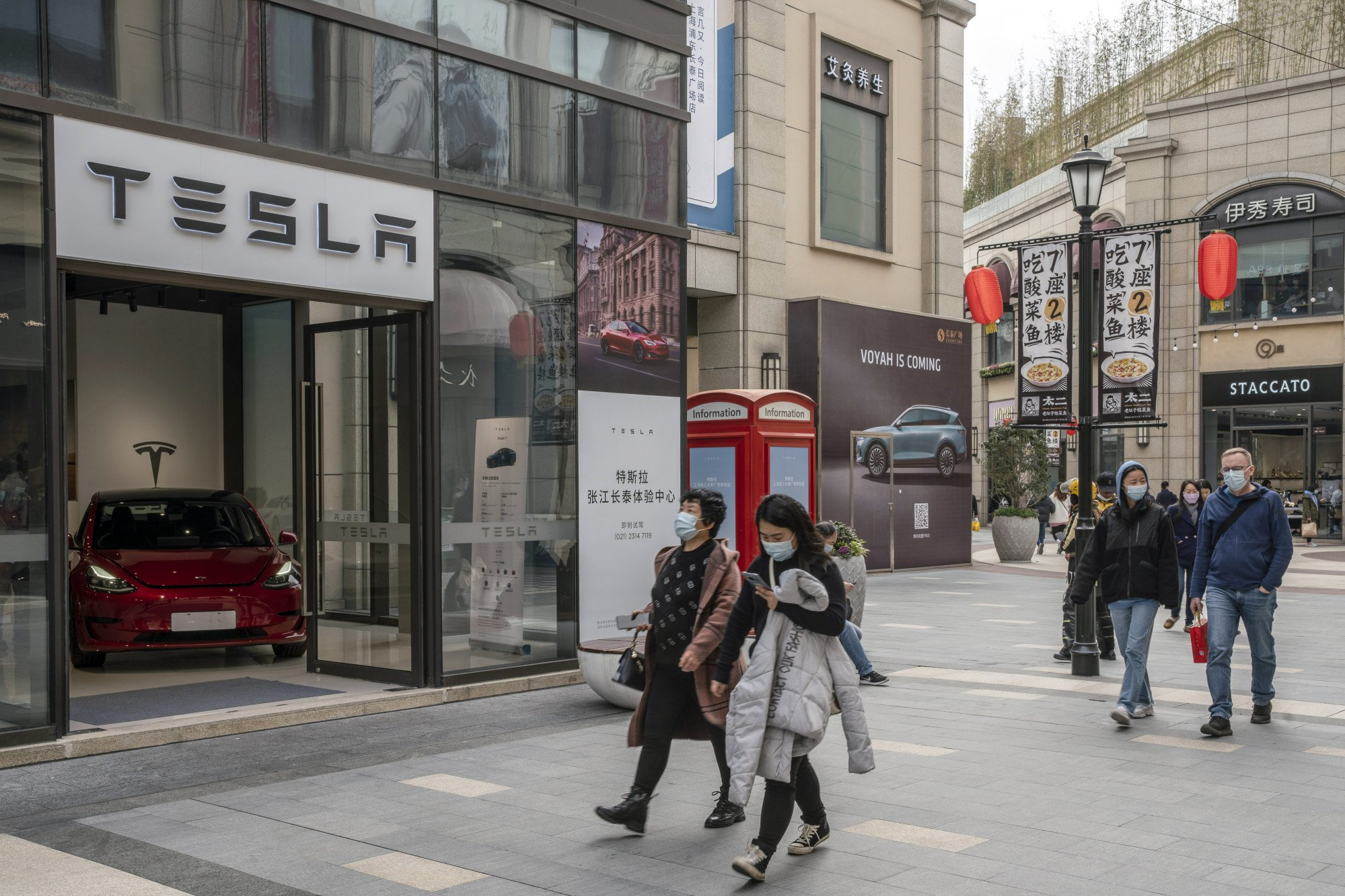 Shoppers walk past a Tesla  showroom at the Chamtime Plaza in Shanghai, China. Photo: Bloomberg