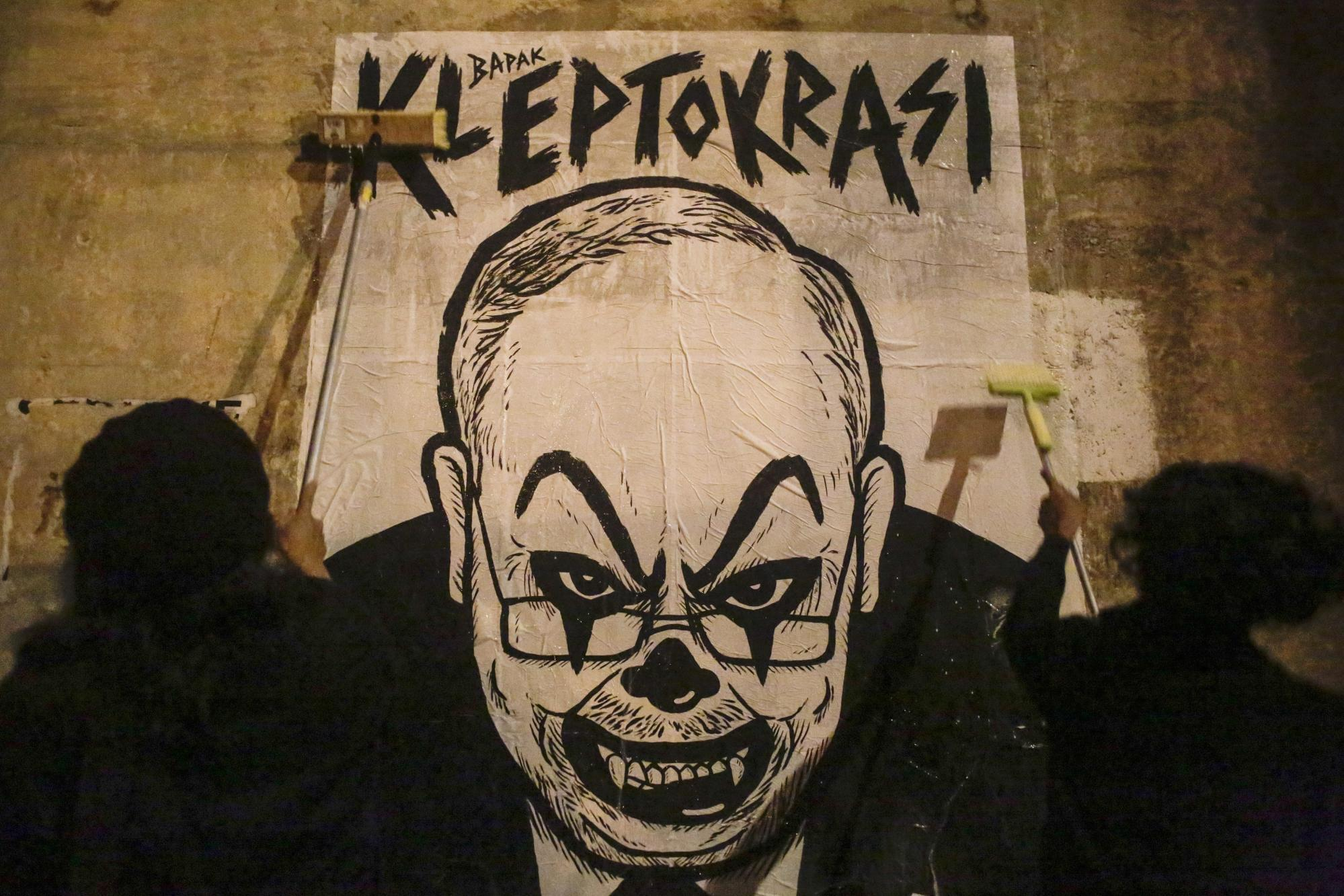 Activist and artist Fahmi Reza and his friend mount a poster depicting Najib Razak with a clown face in 2016. Photo: EPA
