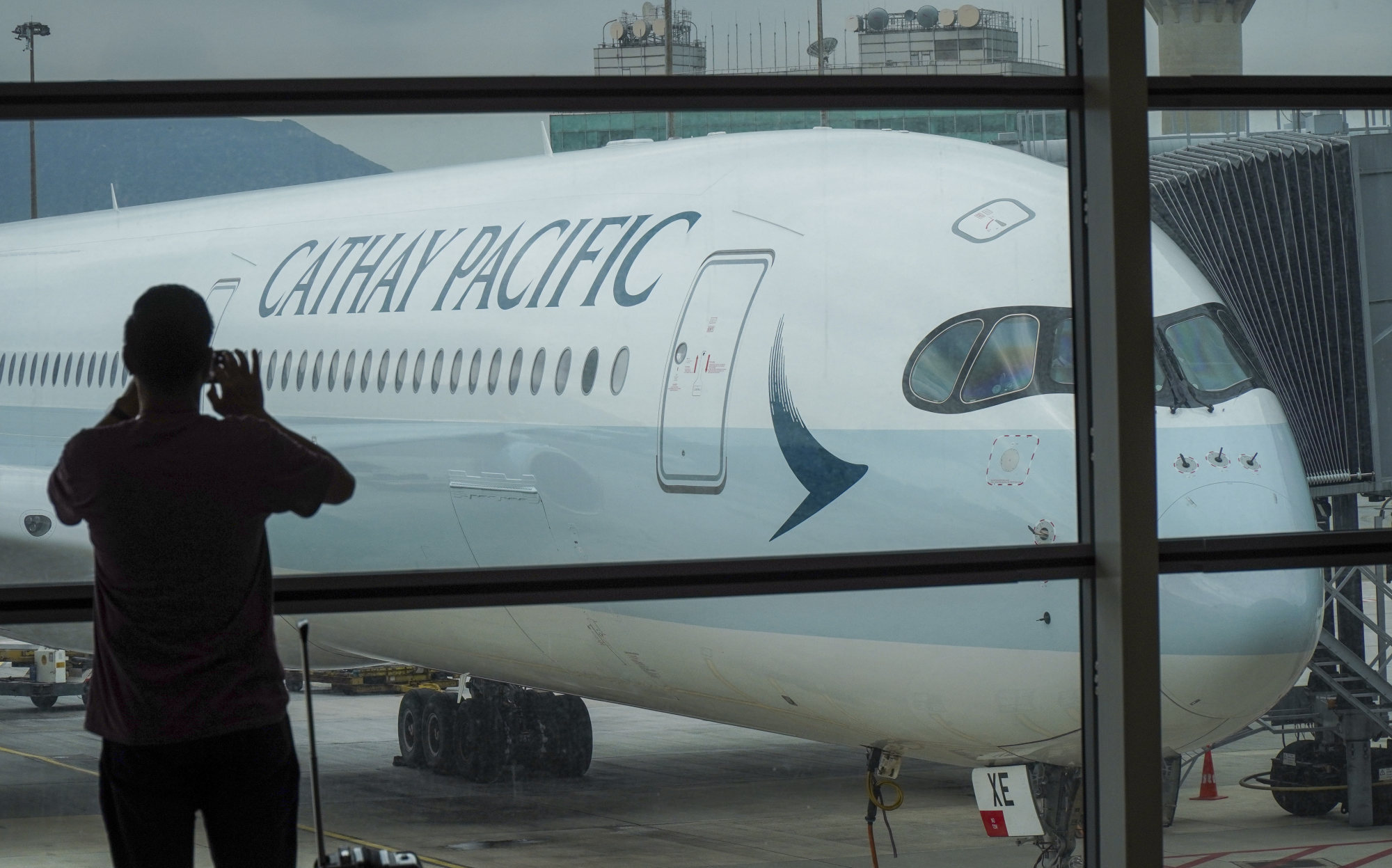 A traveller takes a picture of a Cathay Pacific A350-1000 aircraft parked at Hong Kong International Airport. Photo: Roy Issa