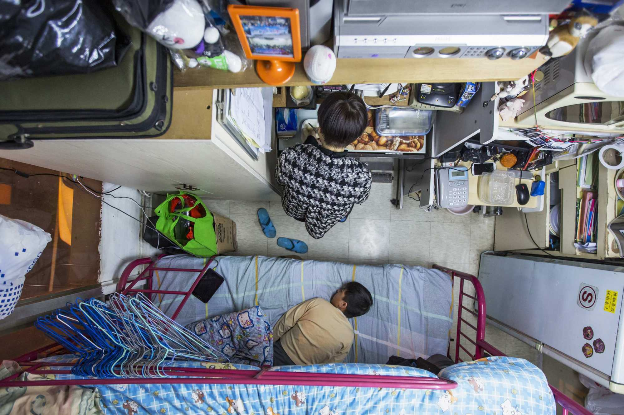 A woman and her son in their subdivided flat in Hong Kong. Some students, embarrassed by their home environments, have refused to turn on their cameras while learning at home. Photo: Reuters