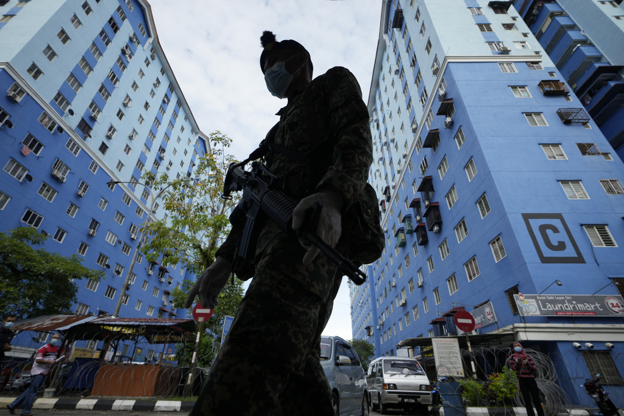 An armed soldier stands guard outside a high-density residential area placed under the enhanced movement control order, in Bukit Jalil, on the outskirts of Kuala Lumpur, Malaysia, on July 11. Photo: AP