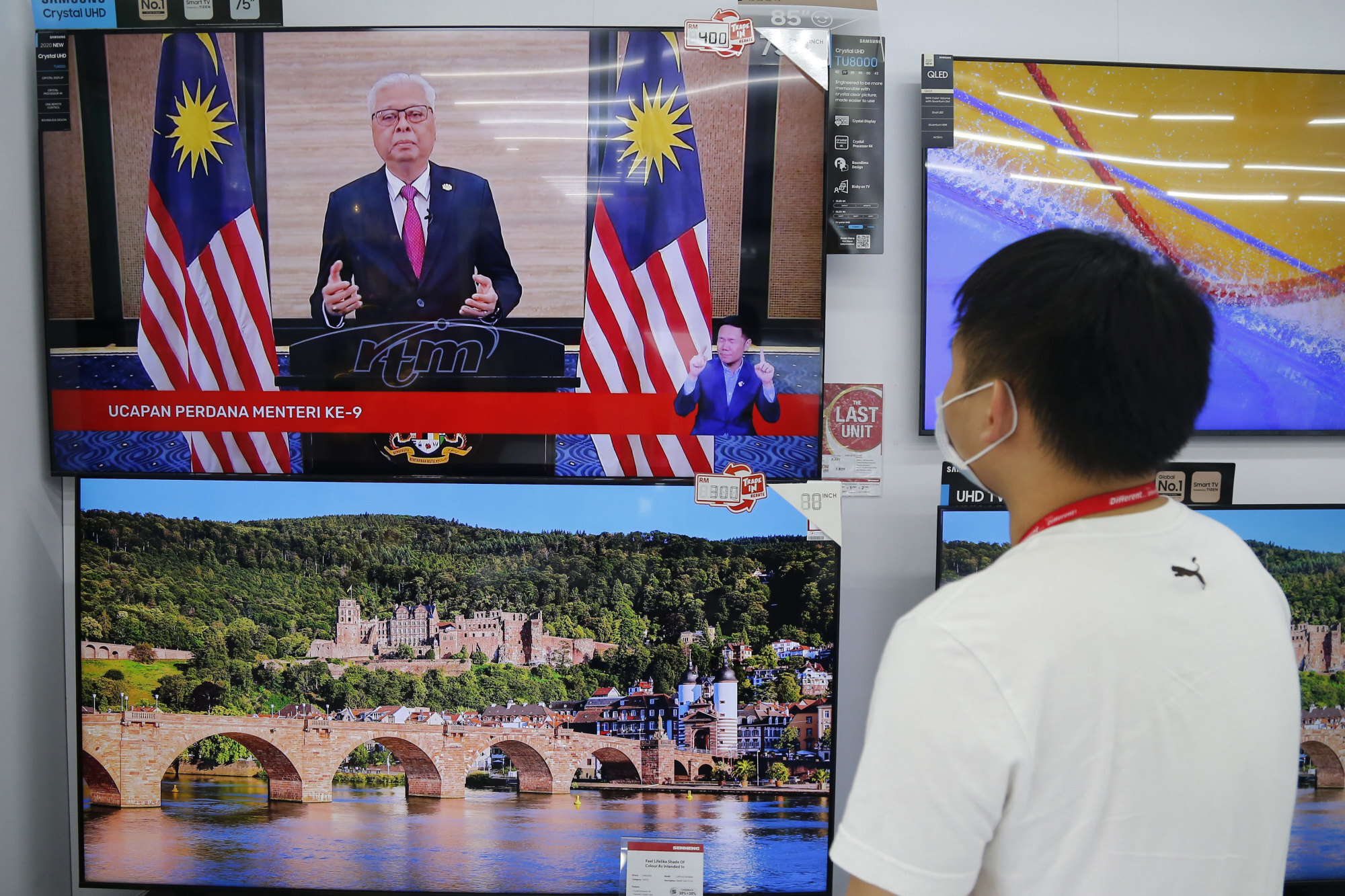 A shop worker watches a speech by Malaysia's new Prime Minister Ismail Sabri Yaakob on television in Shah Alam. Photo: AP