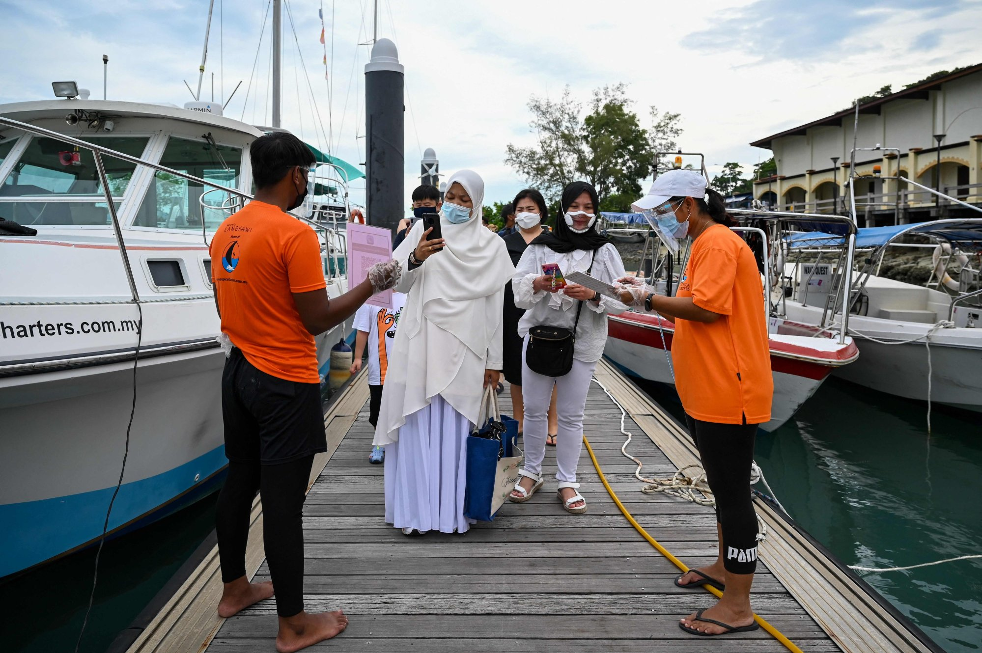 Passengers have the MySejahtera app, used to monitor the Covid-19 coronavirus status, scanned before boarding a yacht in Langkawi. Photo: AFP