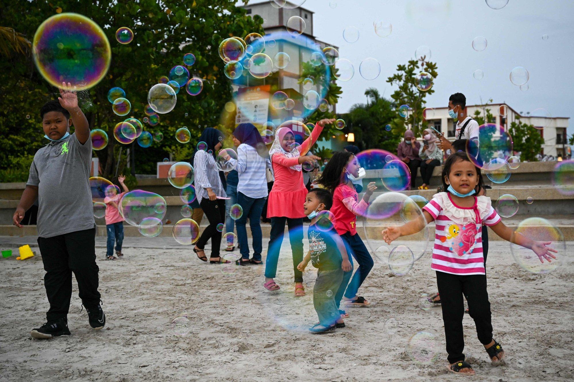 Children play with bubbles at Pantai Cenang in Langkawi. Photo: AFP