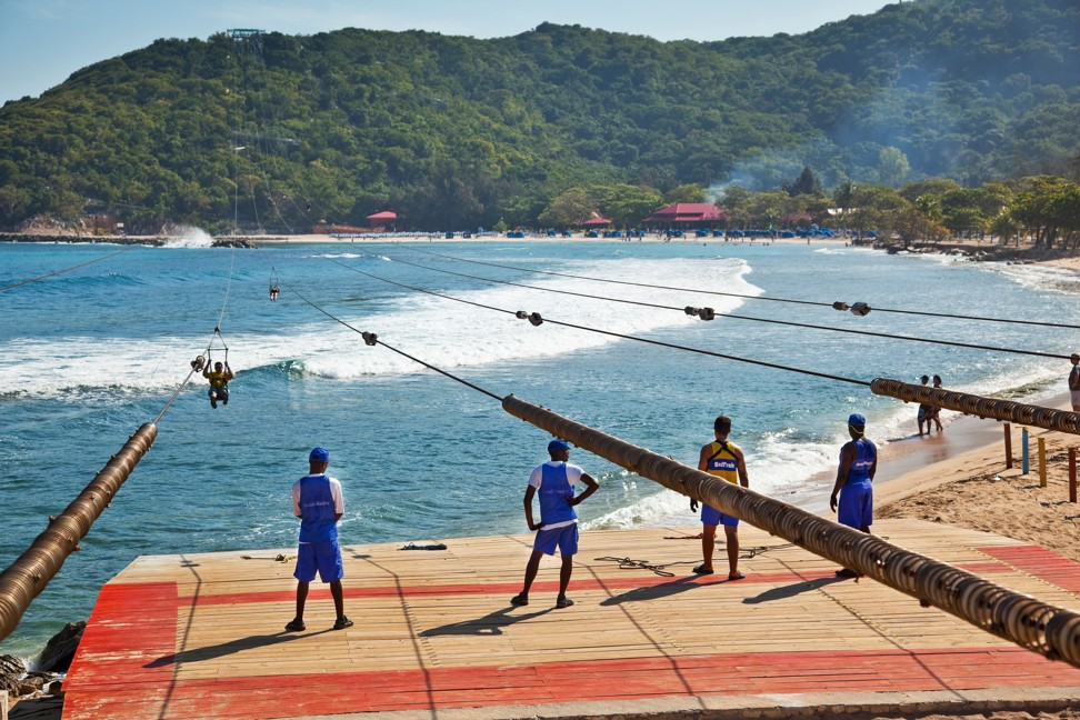 Tourists zip-line in Labadee, Haiti, under the watchful eyes of armed guards, who keep the locals at bay. Photo: Alamy