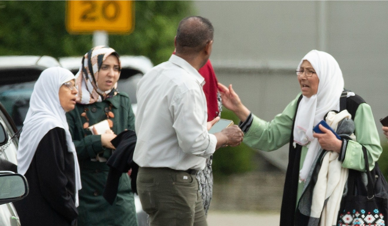 Members of a family react outside the mosque. Photo: Reuters