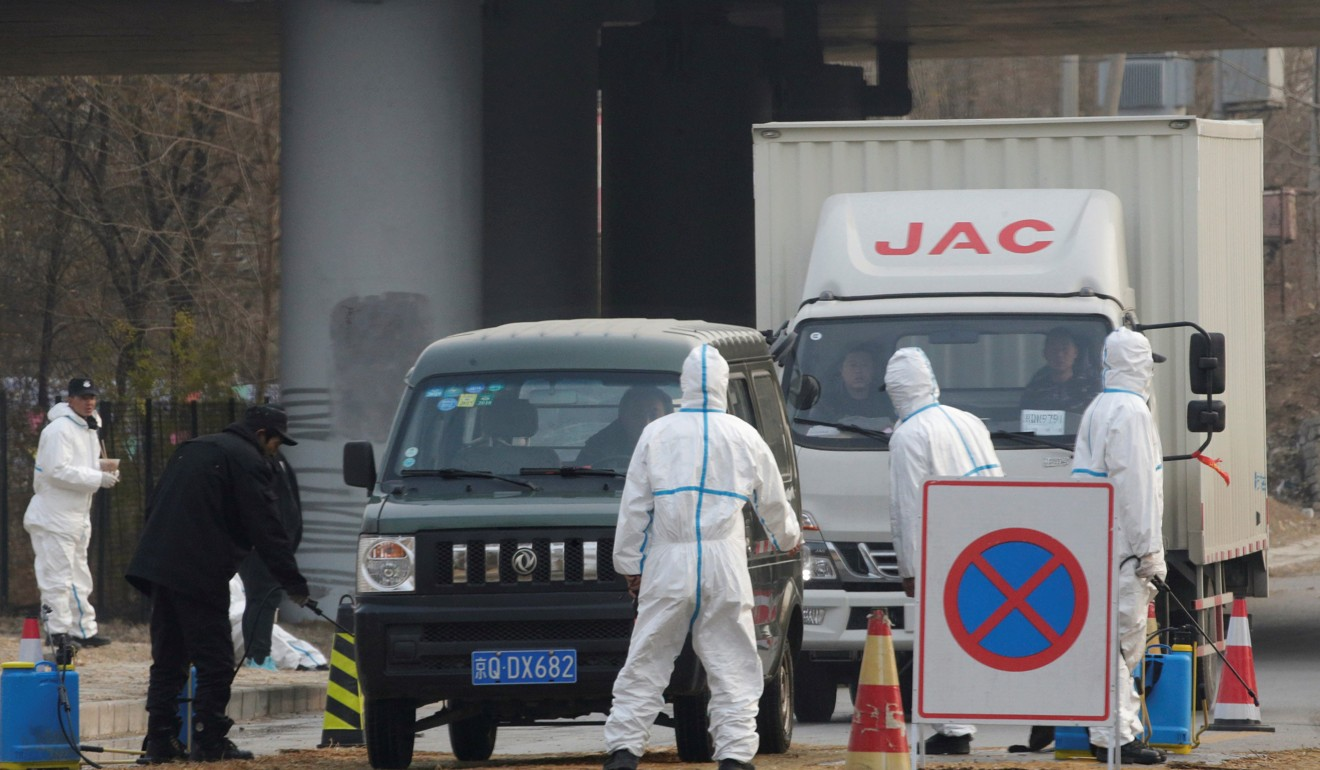 Workers in protective suits at a checkpoint on a road leading to a village near a farm where African swine fever was detected, in Fangshan district of Beijing, China, in November. Photo: Reuters