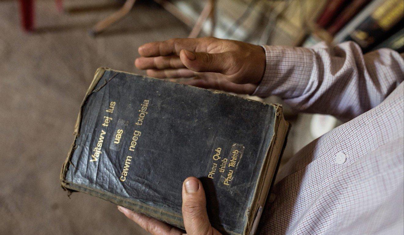 Vang holds a Bible. Photo: Josep Prat