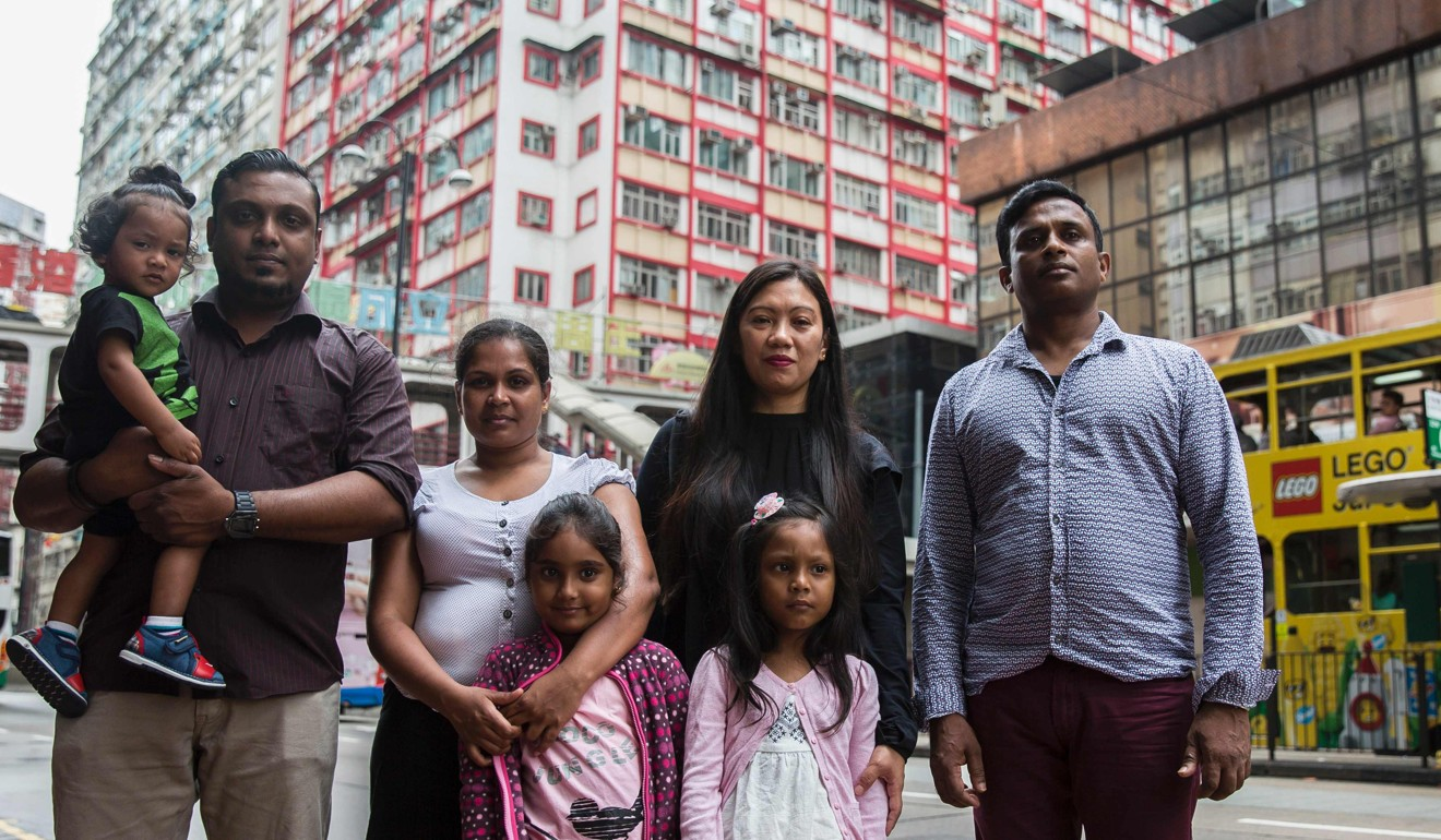 Ajith Pushpakumara, right, Vanessa Rodel, second from right, with her daughter Keana, Nadeeka Dilrukshi Nonis, third from left, and Supun Thilina Kellapatha, second from left, and their children pose for a photo in front of the Torture Claims Appeal Board building in Hong Kong in July 2017. Photo: AFP
