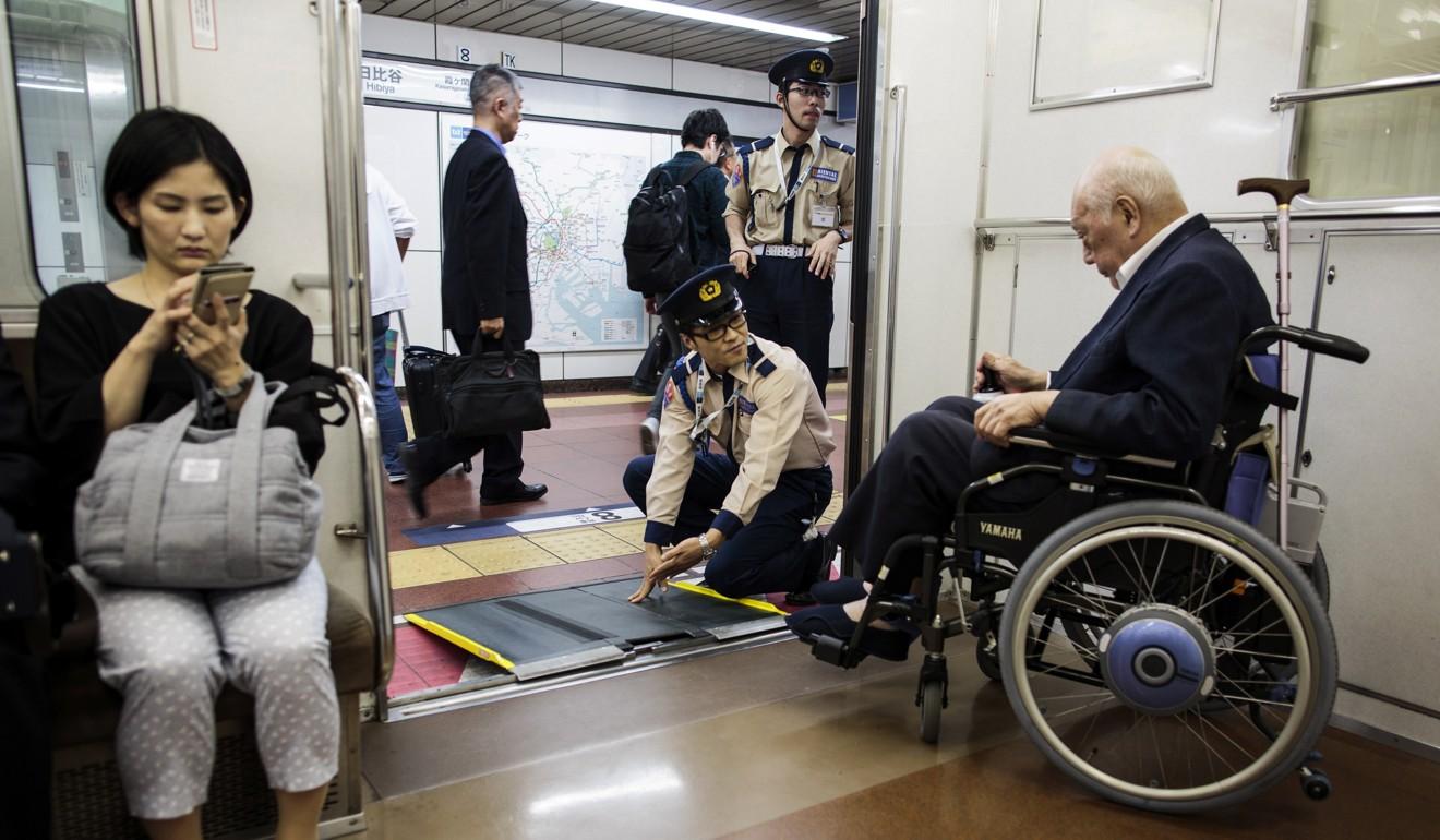 Nhân viên tàu điện ngầm giúp một người đàn ông lớn tuổi ngồi xe lăn xuống tàu tại một nhà ga ở Tokyo vào tháng 5 năm 2017. Ảnh: AFP