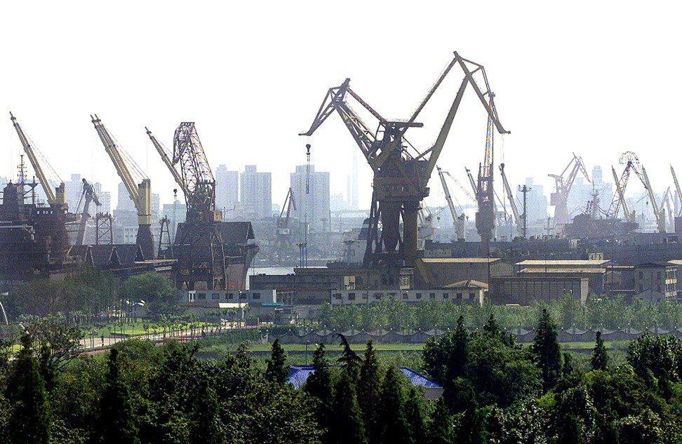 Rows of gantry cranes standing along the Huangpu River in Shanghai on 26 June 2002. A consortium of Chinese domestic banks provided a 17 billion yuan (US$2 billion) credit line toward the construction of Shanghai's Yangshan deep-sea container port. Photo: AFP