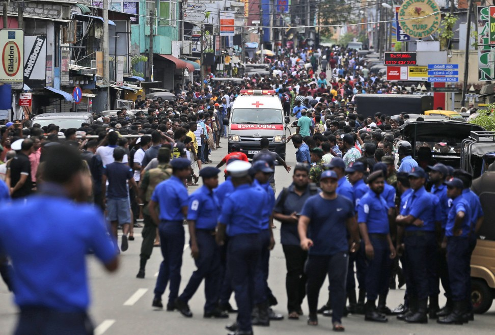 Sri Lankan police officers clear the road as an ambulance drives through carrying injured away from one of the attacks in Colombo. Photo: AP