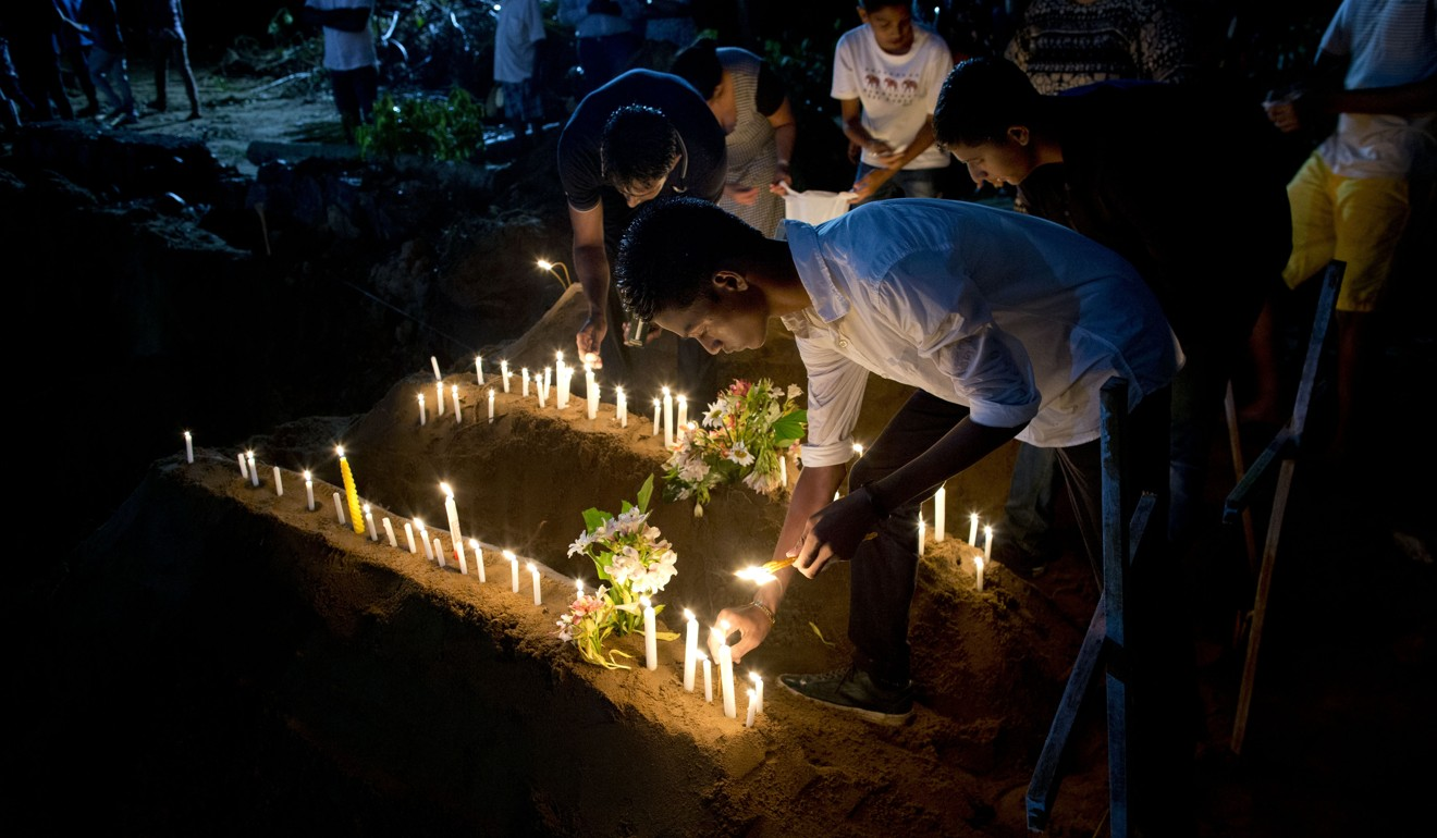 Relatives light candles on Monday after the burial of three victims of the Easter Sunday bomb blasts in Sri Lanka. Photo: AP