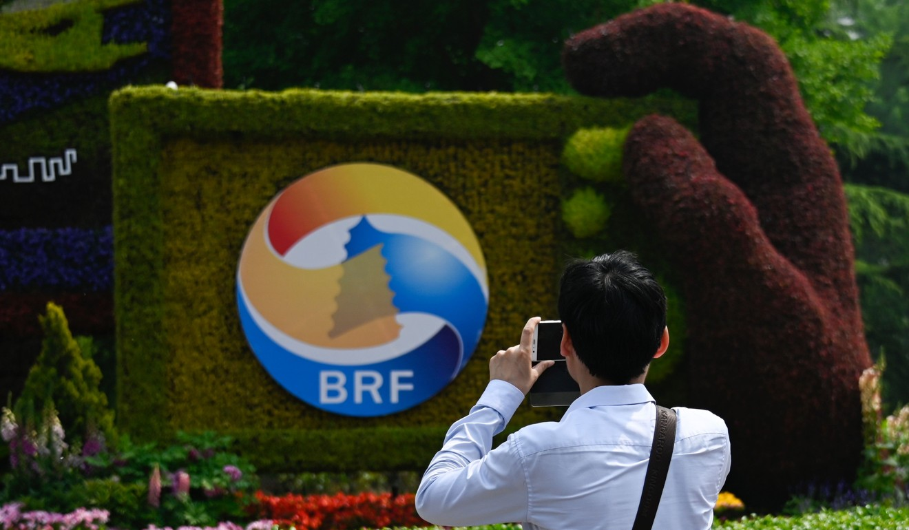 A man takes photo of a sign promoting the Belt and Road Forum in Beijing. Photo: AFP