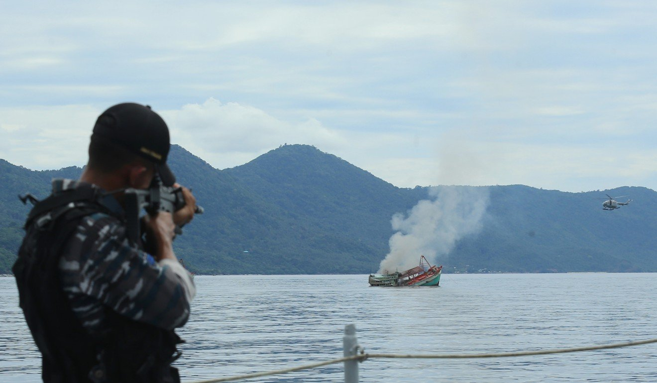 An Indonesian Navy officer targets a seized Vietnamese boat fishing to sink in 2014. Photo: AFP
