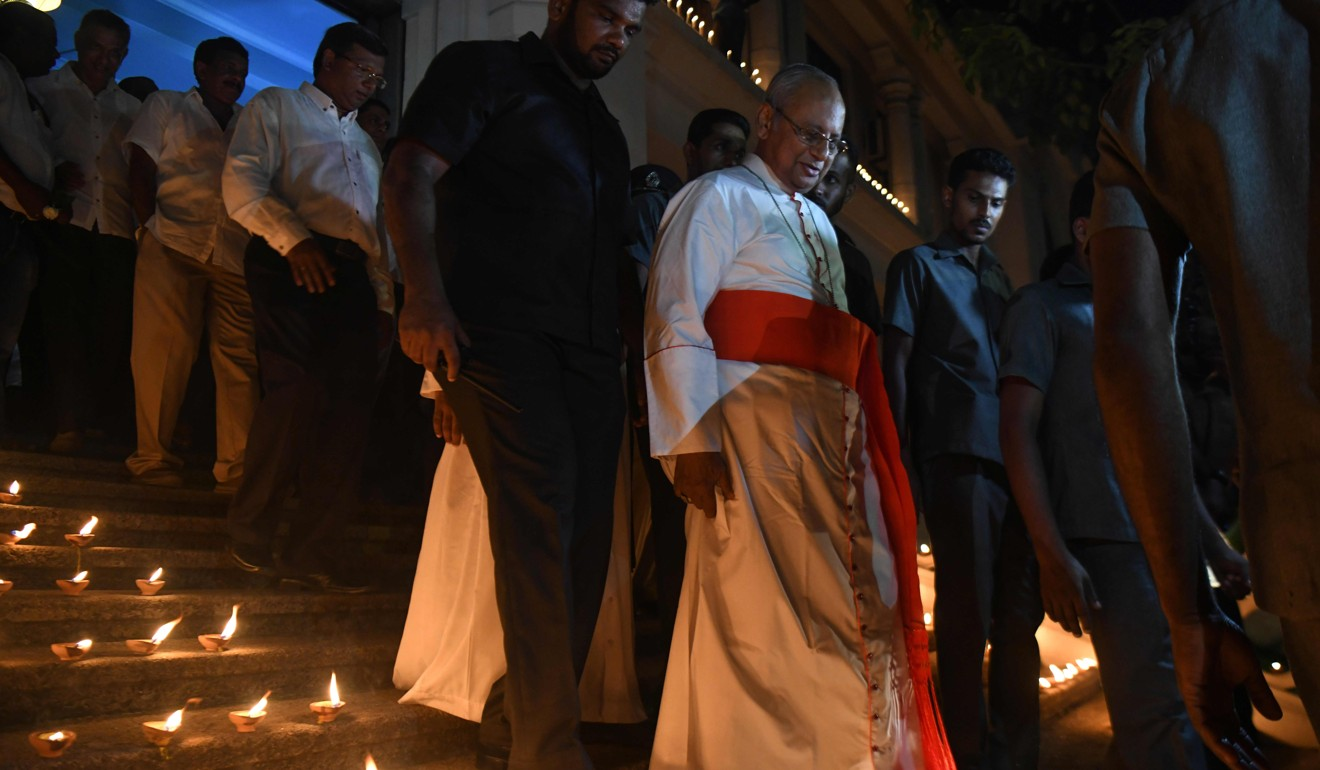 Cardinal Malcolm Ranjith (centre) attends a candlelight vigil on Sunday in memory of bombing victims in Colombo. Photo: AFP