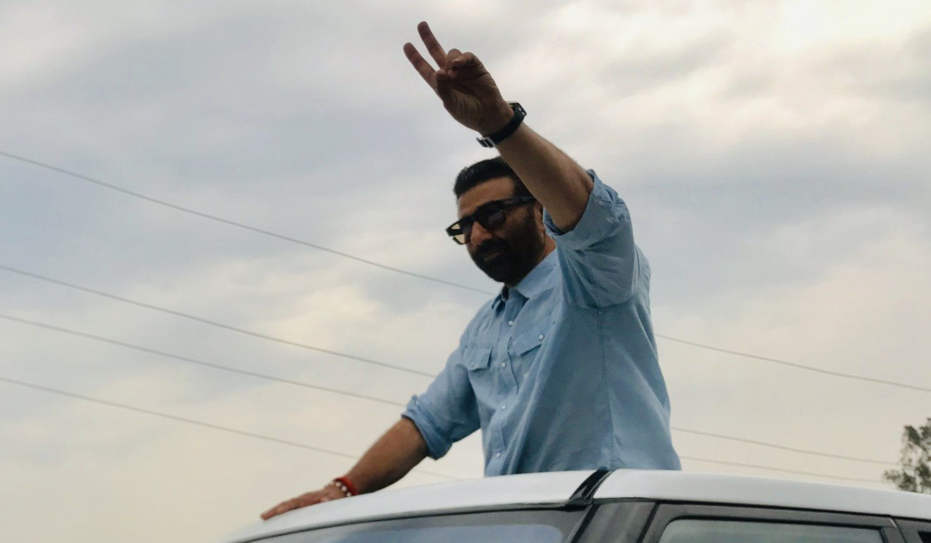 Deol waves to voters from the sunroof of a car in Gurdaspur. Photo: Sonia Sarkar