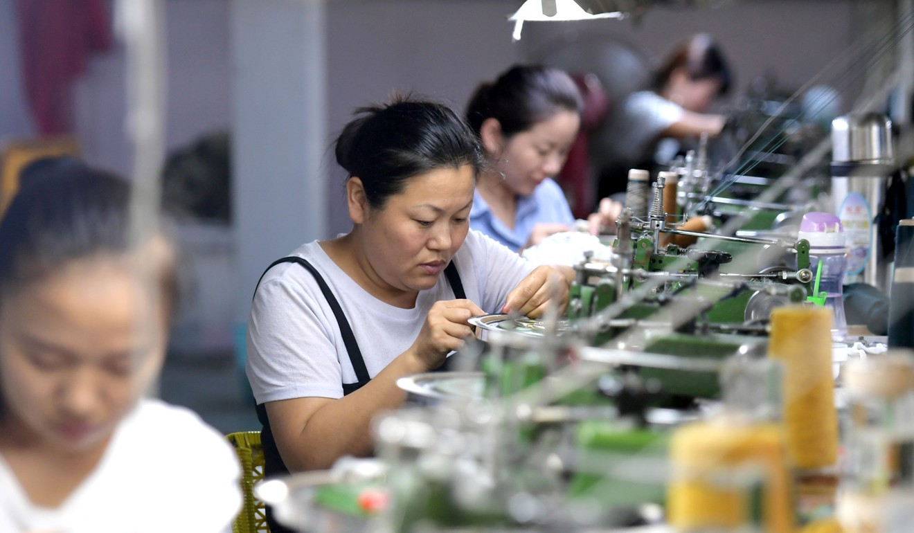 Employees work on the production line of clothes for export at a factory in Xiayi county in China's central Henan province in August 2018. Photo: AFP