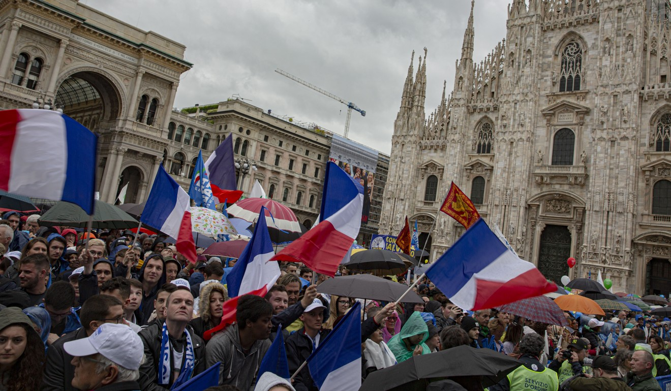 Attendees wave French flags during the campaign rally. Photo: Bloomberg