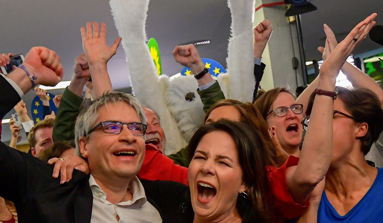 German Greens party top candidate Sven Giegold and co-leader Annalena Baerbock celebrate as exit polls are announced. Photo: AFP