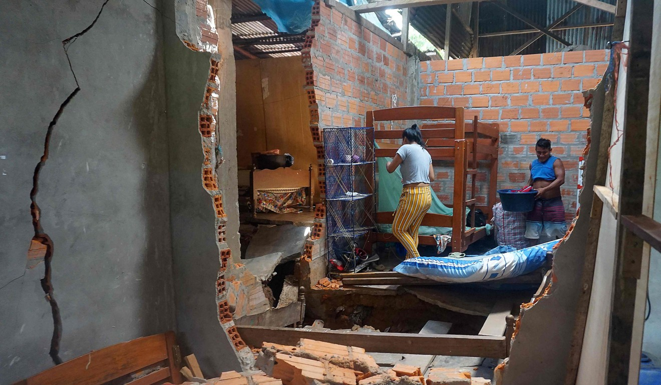 People salvage belongings after a quake damaged their house in Yurimaguas, in the Peruvian Amazon region, on Sunday. Photo: AFP