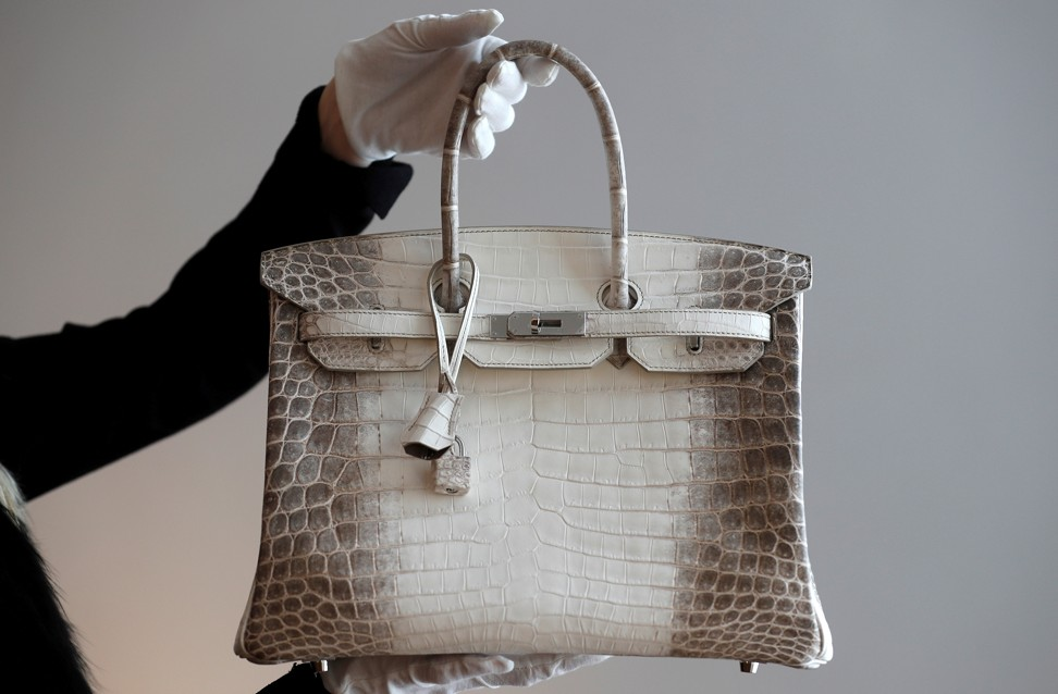 Một nhân viên của Christie cầm một chiếc túi da cá sấu màu trắng quý hiếm từ bộ sưu tập Hermès Himalaya ở Paris trước một cuộc đấu giá năm 2016. Một chiếc túi có cùng kiểu dáng được bán với giá 2 triệu đô la Hồng Kông ở Hồng Kông trong tuần này. Ảnh: Reuters