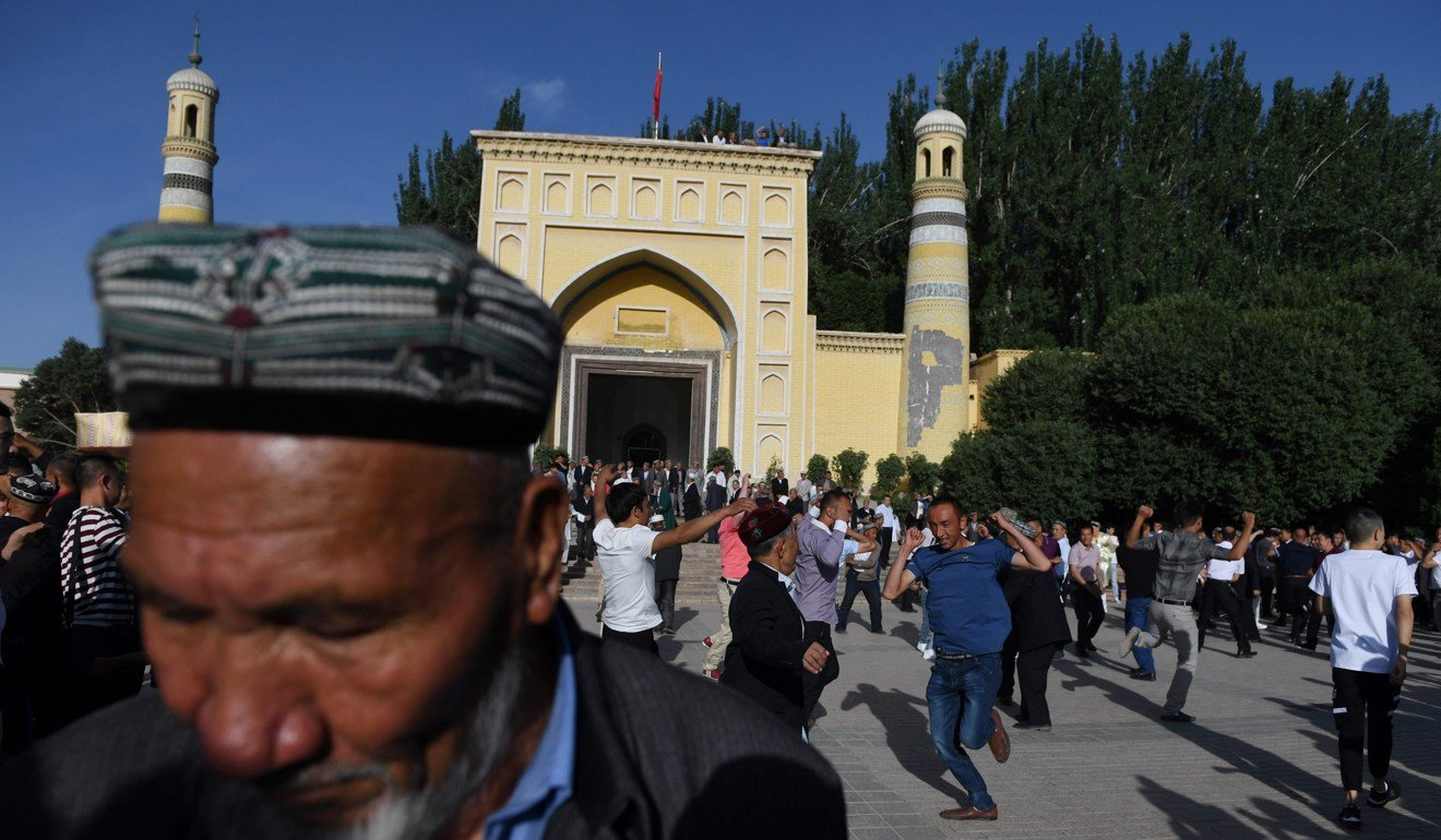 Uygur men dance after Eid al-Fitr prayers in Kashgar. Photo: Greg Baker/ AFP
