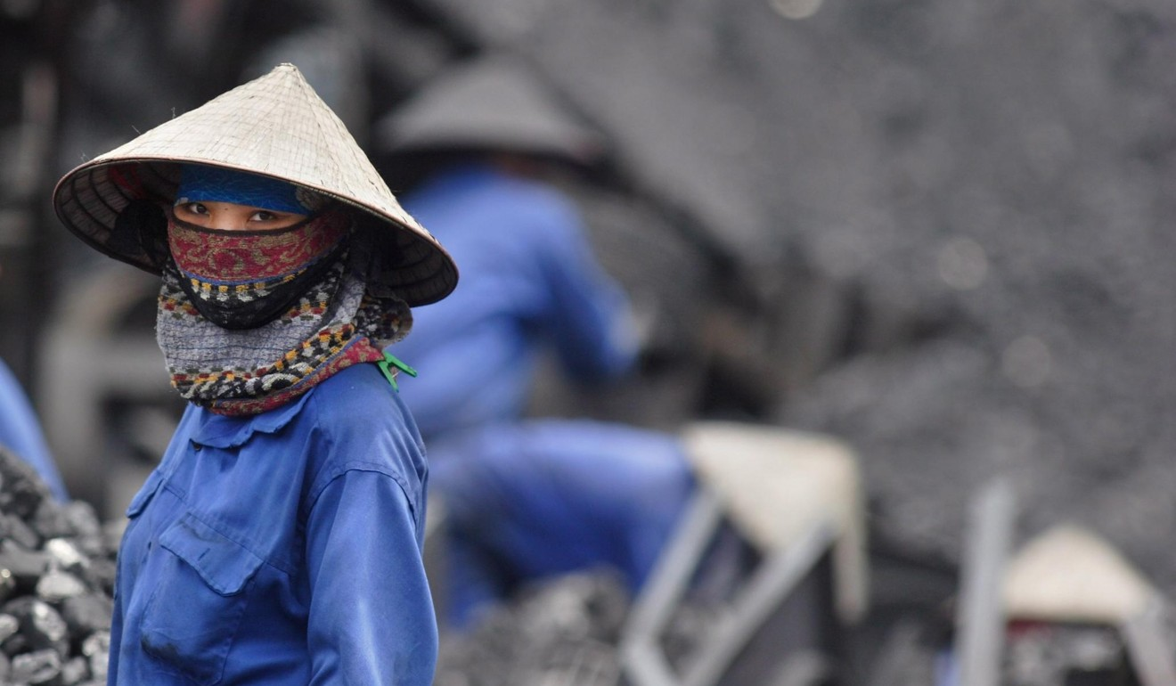A miner takes a short break from sorting through coal in Uong Bi in Vietnam's northern Quang Ninh province in April 2007. Photo: EPA