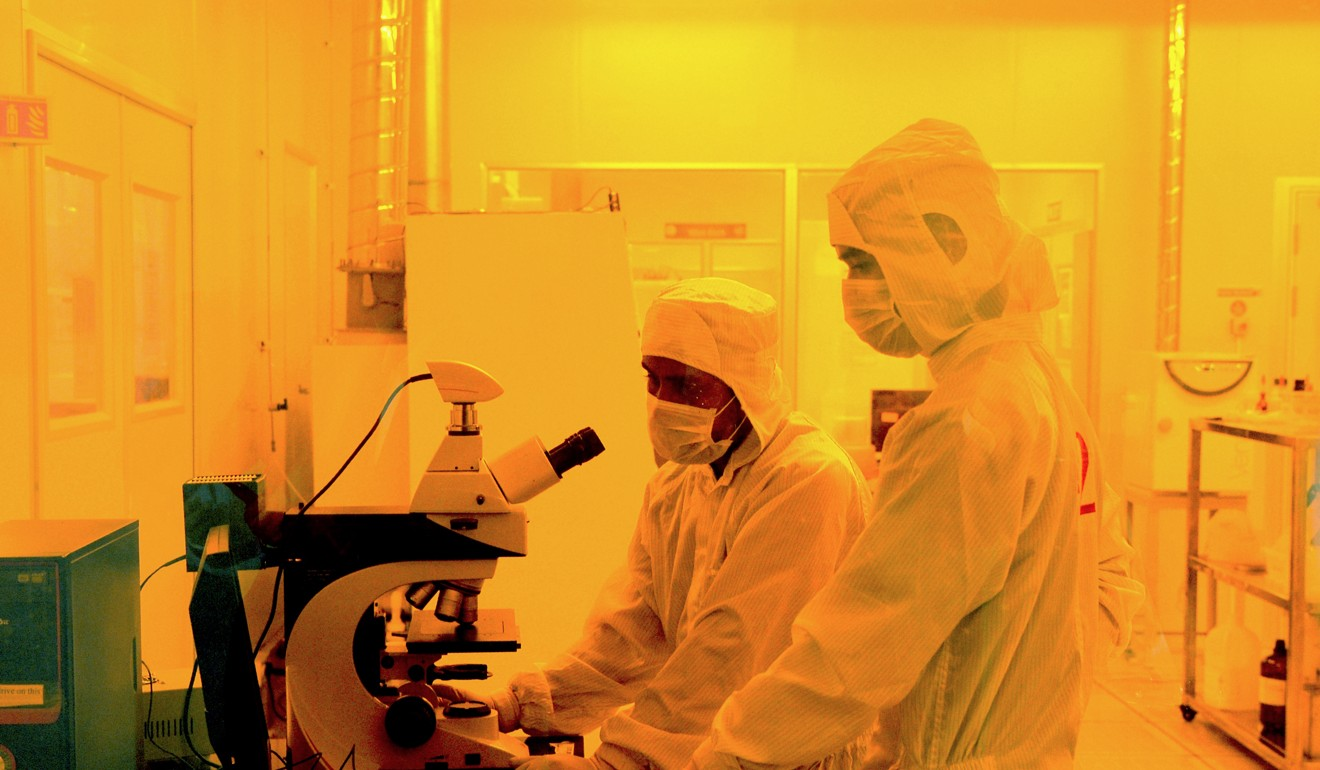 Researchers wearing suits work inside a semiconductor fabrication lab. China is 10 years behind the US in chips, according to one expert. Photo: AFP