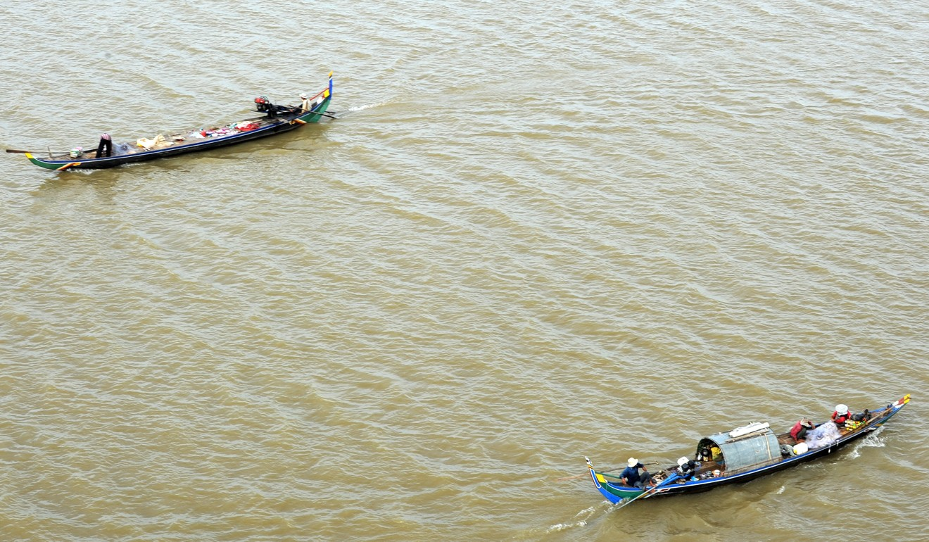 A Cambodian fishing family drive their boat in the Mekong River on the outskirts of Phnom Penh. Photo: AFP