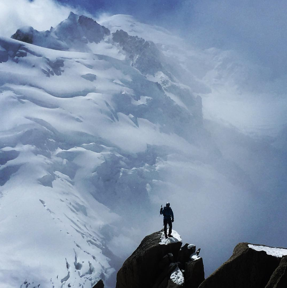 A climber stands atop the Cosmique with Mont Blanc looming in the background. As the sport becomes more popular, officials are struggling to control numbers on Europe's highest peak.