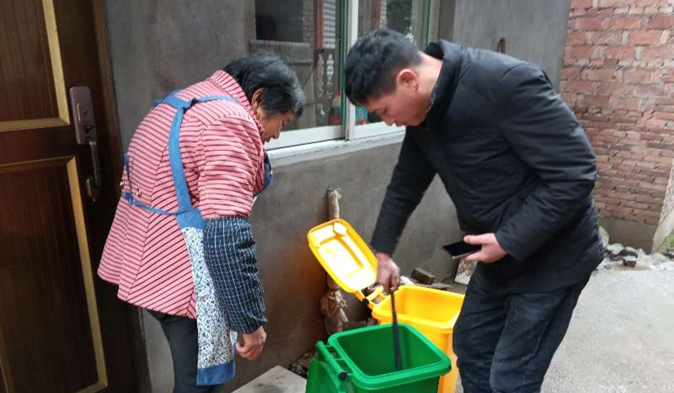A government official in Dongyang county checks if a woman has correctly sorted her rubbish. Photo: Handout