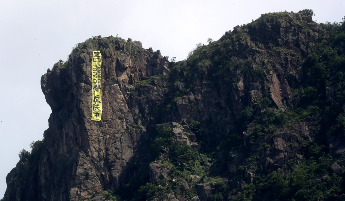 Lion Rock has became a symbol of defiance during protests in the city, with a banner reading 'No Extradition to PR China'. Photo: Edmond So