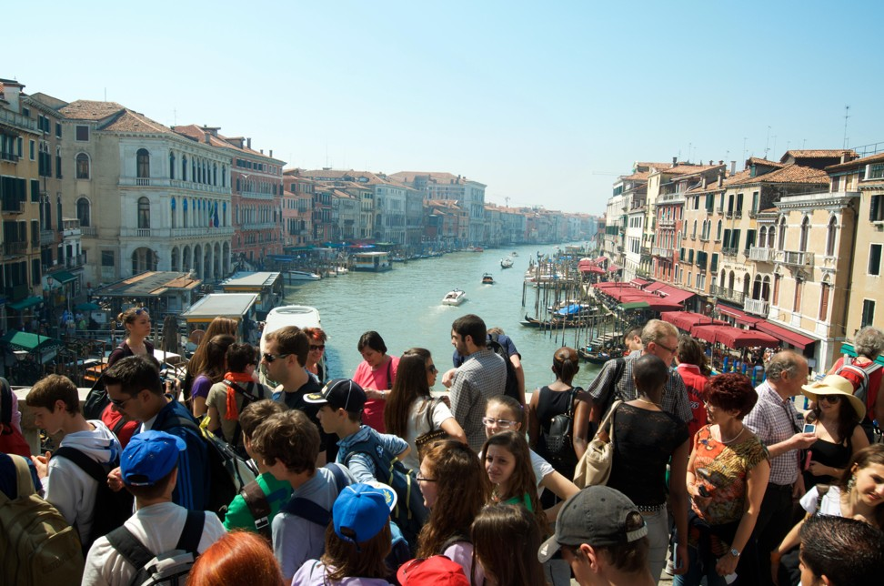 Tourists crowd onto Venice's Rialto Bridge. Photo: Alamy