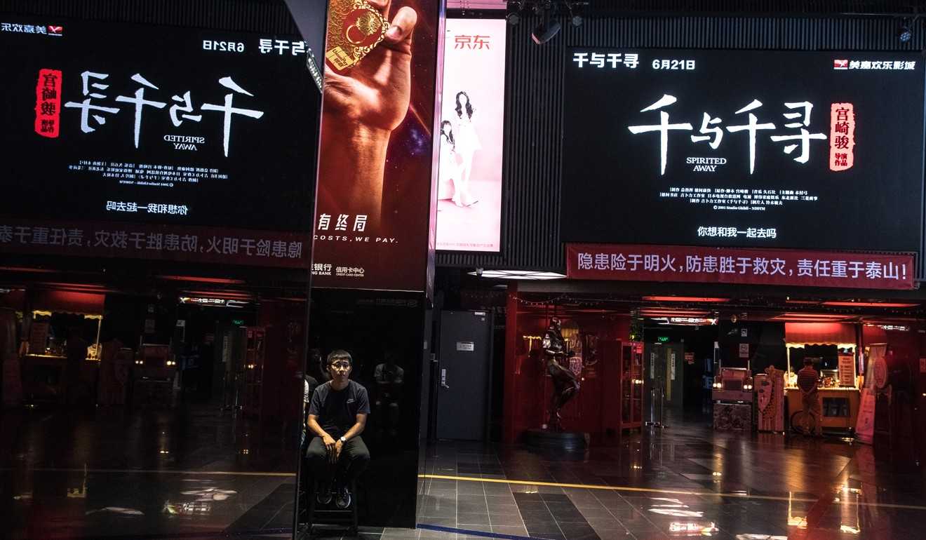 A visitor sits at a cinema's hall as a trailer for Spirited Away shown on a big screen in Beijing on Thursday. Photo: EPA-EFE