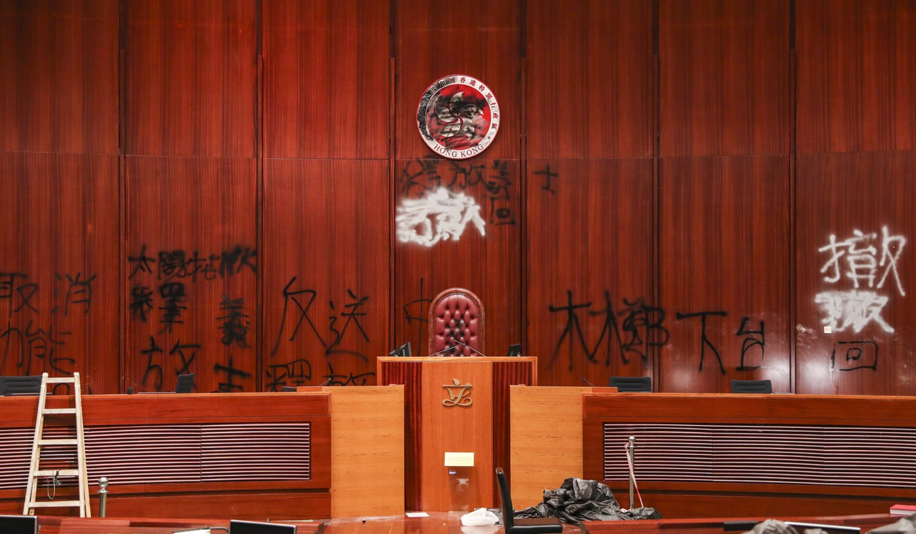 Graffiti on the wall and regional emblem of the HKSAR at the Legco chamber. Photo: Sam Tsang