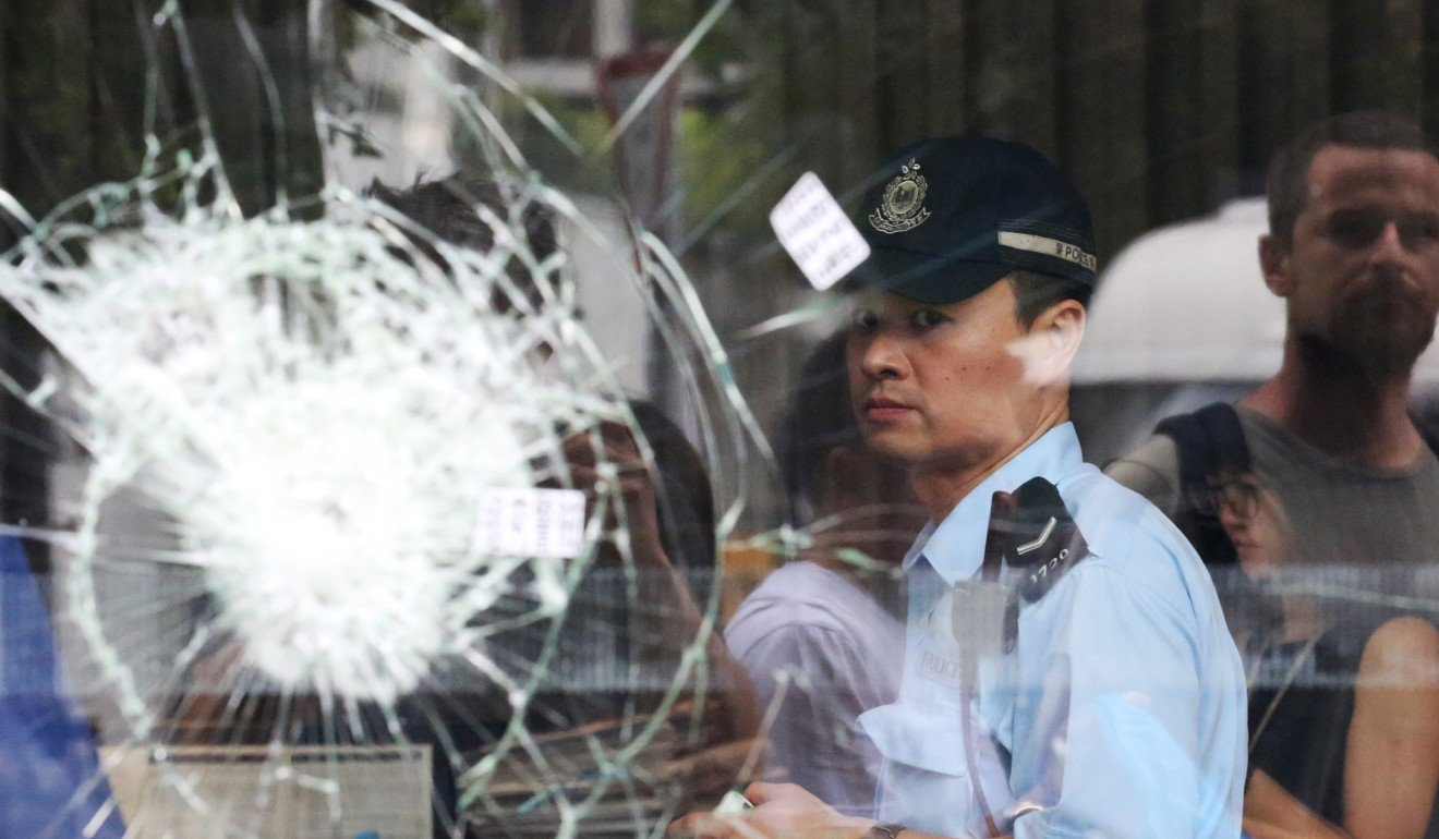 A policeman behind broken glass panels at Hong Kong's Legislative Council Building after protesters stormed the building. Photo: EPA