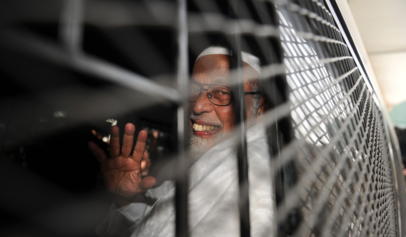 Radical Indonesian cleric Abu Bakar Bashir waves from a police vehicle after he was convicted by a Jakarta court for terrorism in June 2011. Photo: AFP