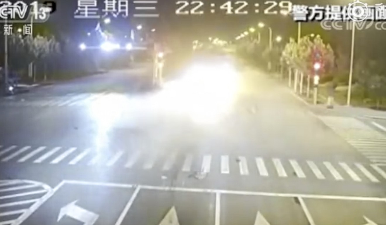 The BMW bursts into flames after being shoved across the intersection. Photo: Weibo