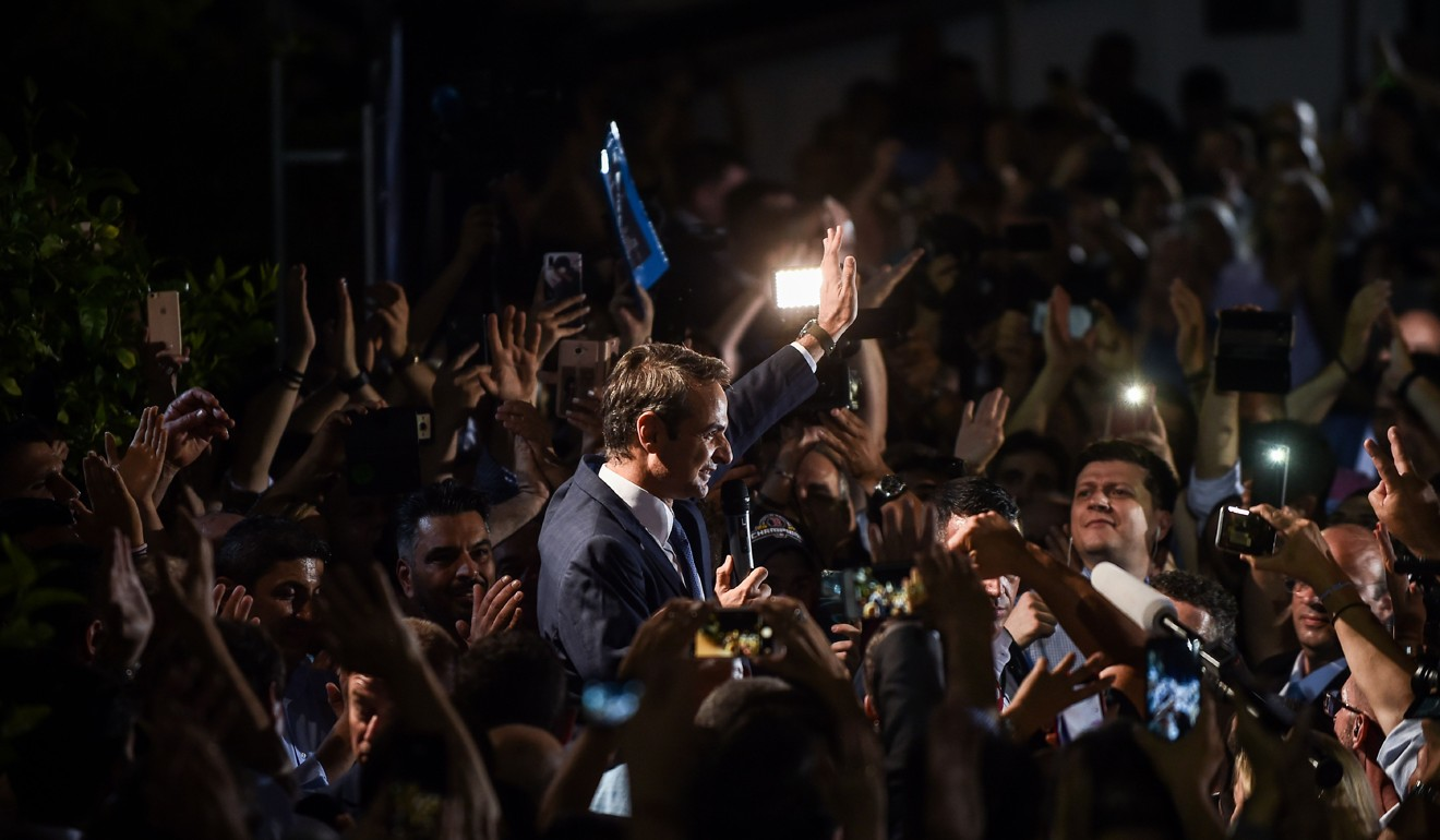 Greece's newly elected Prime Minister and leader of conservative New Democracy party Kyriakos Mitsotakis, waves at his supporters outside the party's headquarters on Sunday. Photo: AFP