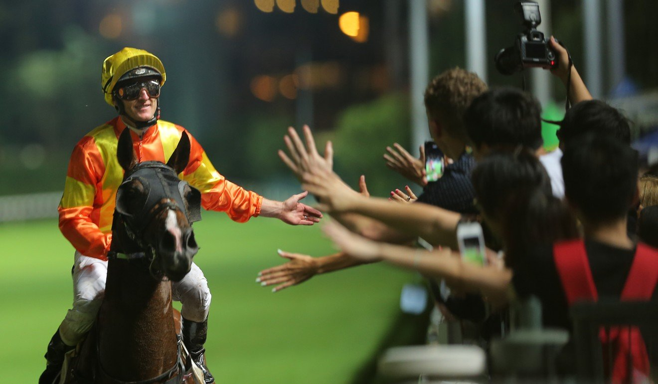 Zac Purton high-fives the fans after winning with High Rev on Wednesday night.
