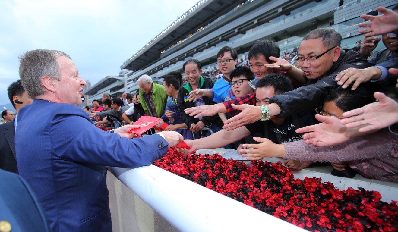 Jockey Club chief executive Winfried Engelbrecht-Bresges hands out red packets to punters.