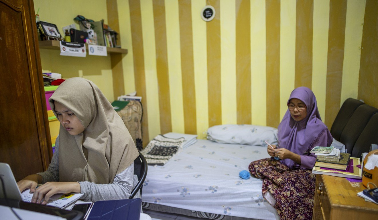 Rizka at work in a room with her mother. Photo: Unicef/Arimacs Wilander
