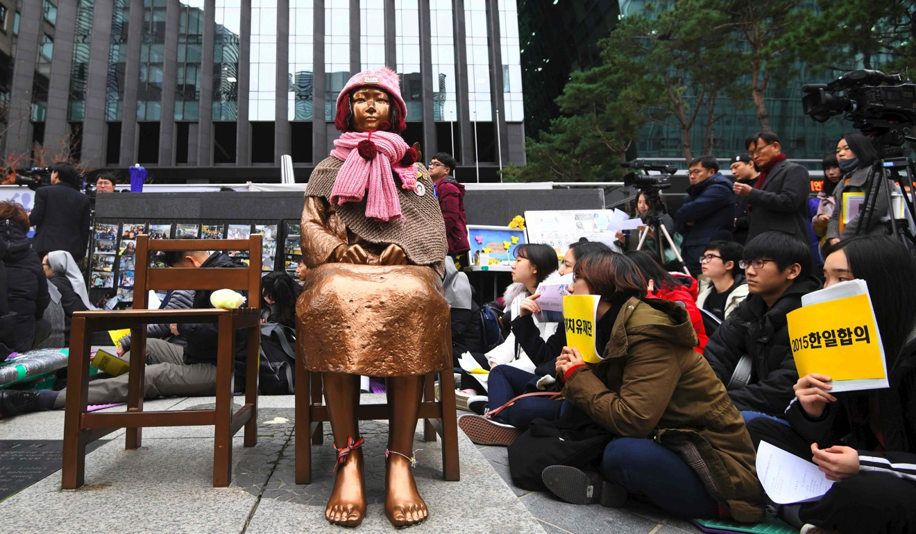 "South Korean protesters sit near a statue of a girl symbolising former ""comfort women"" forced into sexual slavery, at a demonstration in front of the Japanese embassy in Seoul in November 2018. Photo: AFP"